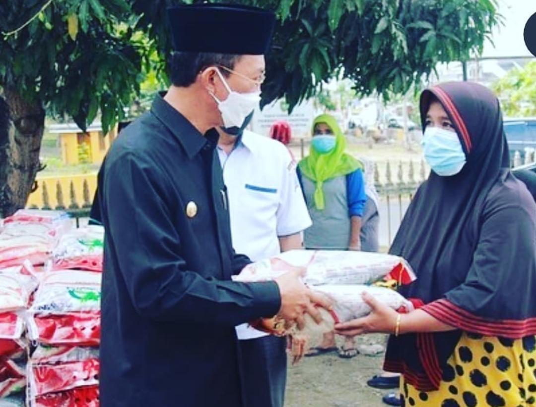 Walikota Palembang H Harnojoyo menyerahkan bantuan 10 kg beras kepada PKM PKH di Kelurahan Bukit Lama.