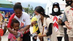 Relawan protokol kesehatan memeberikan masker kain kepada warga di sekitar Stadion Barnaban Yumeo, Senin (27/9)